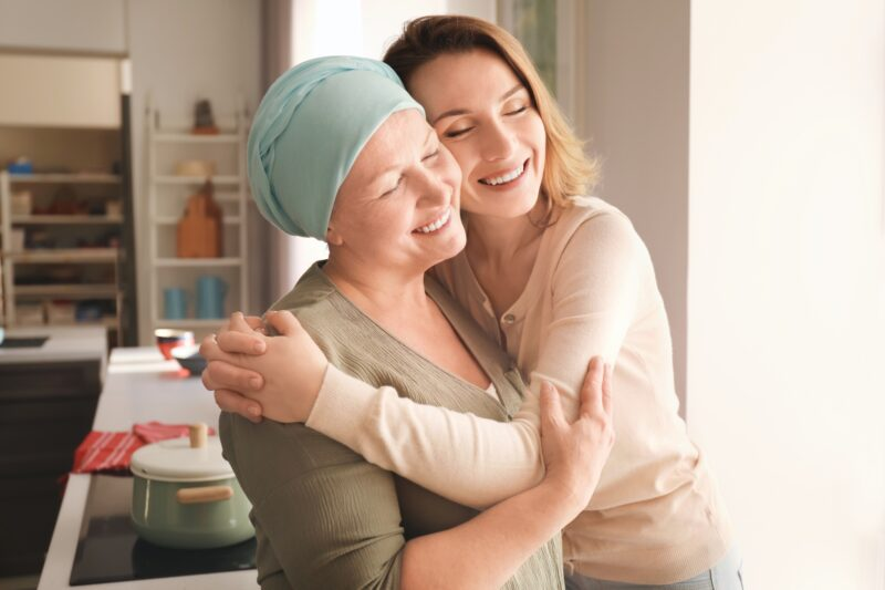 daughter hugging mother who is wearing a head scarf